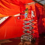 worker on a scissor lift taping off hazardous areas in a demolition with orange sheets | understanding the materials present during demolition